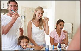 Family Brushing Teeth In Bathroom Mirror