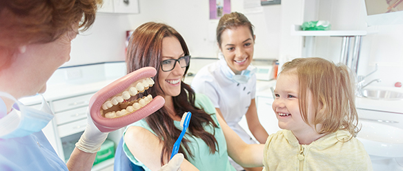A dentist showing a mouthguard to little girl