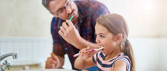 A Girl brushing her teeth with her father