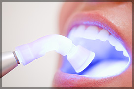 Dentist Performing Teeth Whitening to a Female Patient