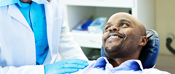 dentist-talking-to-smiling-male-patient-584x248