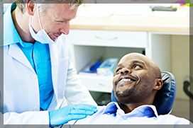 Dentist Talking To Smiling Male Patient Before Oral Surgery