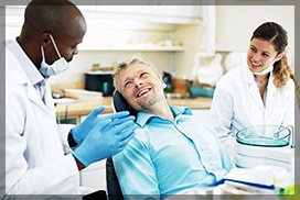 Friendly dentist and his nurse, talking to a male patient