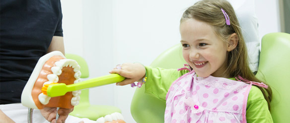 little girl learning to brush with fun at dentist's office in Ottawa